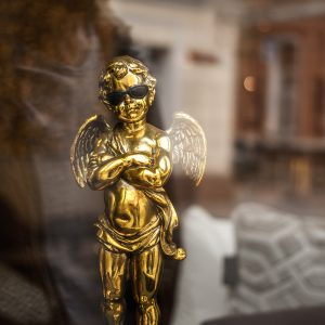 golden cupid statuette wearing sunglasses
