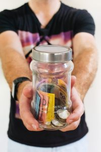 person holding out glass jar with money